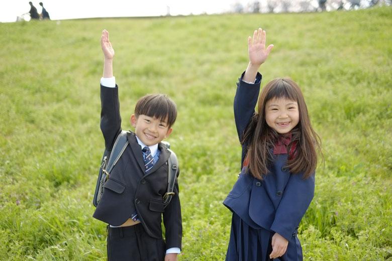 手を挙げる男の子と女の子の写真